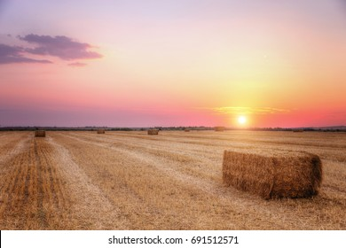 Hay bale in the field against sunset sky