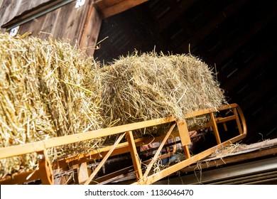 Hay bale on a conveyor belt into the hayloft of a barn.