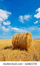 Hay bale on the field beneath cloudy sky
