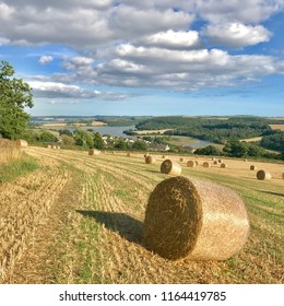 Hay bales in a field with view across the east Cornwall countryside.