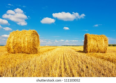 Hay bales on the field beneath cloudy sky