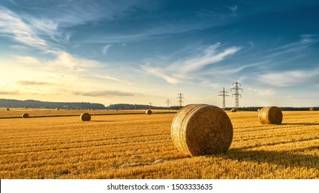 Hay bales on the golden agriculture field. Sunny landscape with round hay bales in summer. Rural scenery of straw stacks at sunset. Panorama of yellow wheat haystacks in countryside. Farm concept.