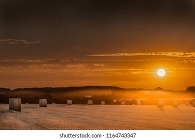 Hay bales at sunset with skies clearing to show stars at night. Beautiful panoramic evening orange sun over rural crop fields in Norfolk