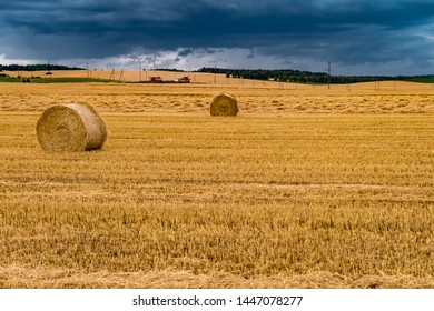 Hay bales under cloudy storm sky on harvested wheat field.