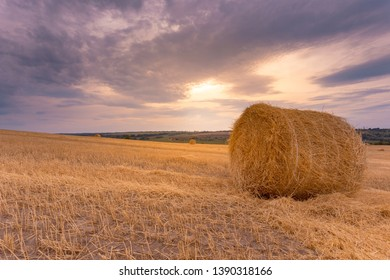 Hay bales under a cloudy sunset sky on a harvested wheat field.