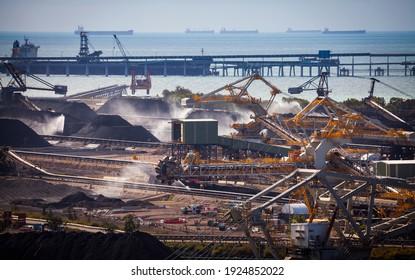 Point de foin. Les terminaux de charbon australiens en vrac. Récipients, convoyeurs et empileurs pour la manutention et l'exportation du charbon. Logos supprimés. Industrie des combustibles fossiles, défi environnemental, changement climatique.