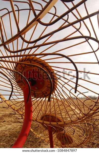 A hay rake sits in a empty field