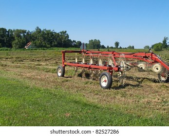Hay rake sitting in a field of just raked hay with farmhouse in the background.