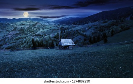 hay shed on a grassy field in mountains. beautiful countryside landscape in springtime at night in full moon light. village on the distant hills