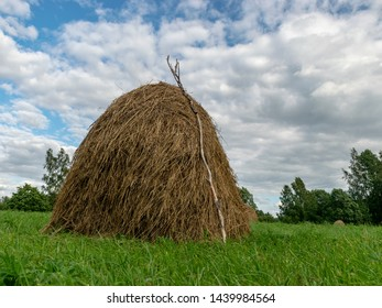 A haystack on the field. Summer countryside landscape with haystack on forest background, concept of agriculture. Rural landscapes. Latvia