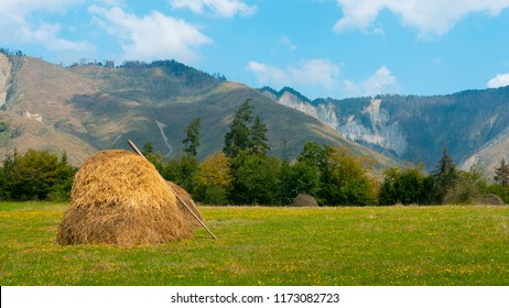 Haystack on a grass with beautiful mountainous background, landscape