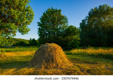 Haystack on a meadow in the village in the evening. Summer season, June.
