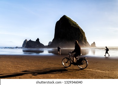 Haystack Rock at Cannon Beach, landmark of the Oregon Coast. Silhouettes of a couple making selfie, bicyclist passing by. Blurred movement. Travel USA.