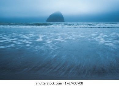 Haystack Rock and Pacific Ocean waves approaching on Oregon Coast beach on foggy overcast morning in Pacific City, Pacific Northwest