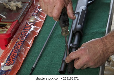 HAYWARD, CA - FEBRUARY 05, 2015: Gunsmith disassembling and reassembling a 20 gauge pump action shotgun for cleaning. Demonstrating safe and proper technique for new gun owners