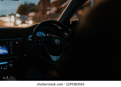 Hayward Heaths, England - October 27th, 2018: Detail of Toyota Auris car steering wheel being driven by young man with the hand on the steering wheel, with night, with right-hand position.