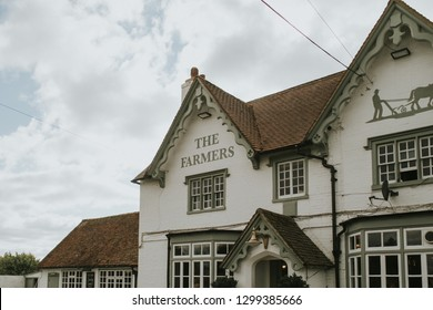 Hayward Heaths, England - October 27th, 2018: The Farmers pub building facade, with blue sky and clouds in the background, in Hayward Heaths, United Kingdom.