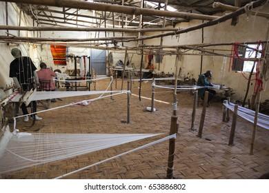HAYZO VILLAGE, DORZE, OMO VALLEY, ETHIOPIA - JANUARY 3, 2014: Unidentified men in traditional Dorze weaving house. Weaving is a main Dorze people business.