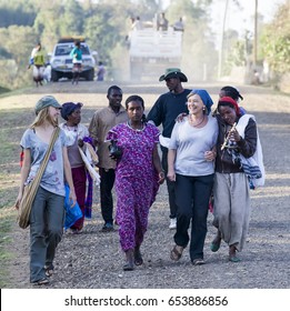 HAYZO VILLAGE, DORZE, OMO VALLEY, ETHIOPIA - JANUARY 3, 2014: Unidentified western tourists surrounded by Local Dorze people.