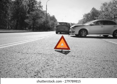 Hazard warning triangle laid out on the road  behind two crashed cars, black and white photo with a  red accent on a triangle