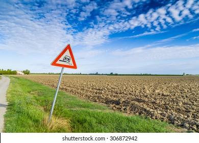 Hazardous Shoulder ruropean road sign along dirt road in Italian countryside on sky background