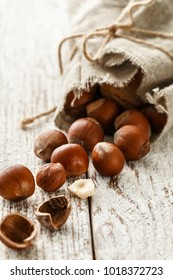 Hazelnut heap on wooden table, selective focus. Healthy food background