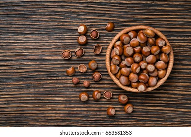 Hazelnut with peeled hazelnuts in brown bowl on textured wooden background, top view.