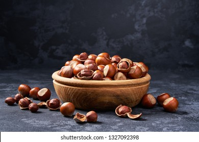 Hazelnut in wooden bowl on black background. Organic hazelnut.