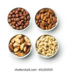 Hazelnuts, almonds, cashew and brazil nuts in bowls isolated on white background. Top view.