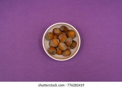 hazelnuts in a bowl on a colored background