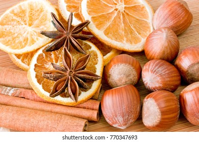 Hazelnuts with cinnamon, anise and orange slices on a cutting board