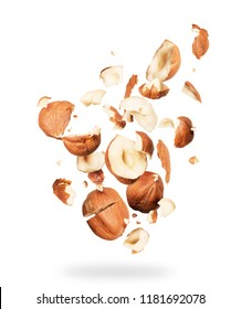 Hazelnuts crushed into pieces, frozen in the air on a white background