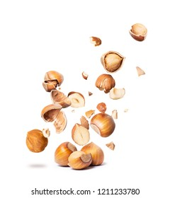Сracked hazelnuts fall down isolated on white background