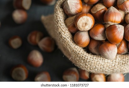 Hazelnuts, filbert in burlap sack on wooden backdrop. heap or stack of hazelnuts. Hazelnut background, healty food
