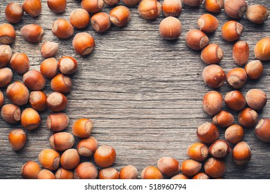 Hazelnuts in form of circle on wood table with copyspace