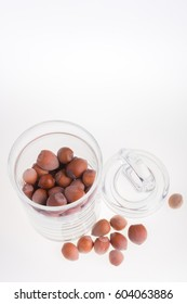 Hazelnuts in glass jar on a white background. Isolated. Dried nuts.
