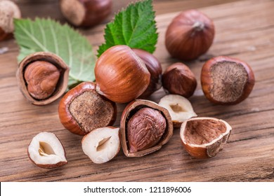 Hazelnuts and hazelnut leaves on the wooden table.