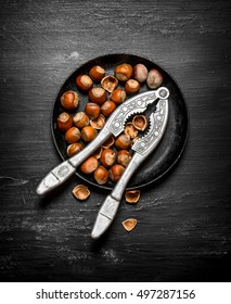 Hazelnuts with Nutcracker on the old plate. On the black wooden table.