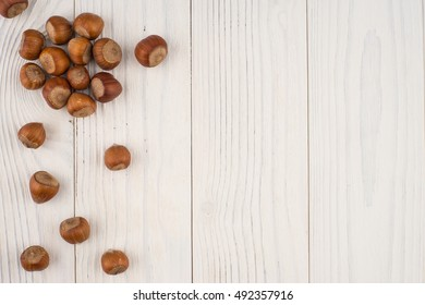 Hazelnuts on a old wooden table. Abstract background, empty template. Top view