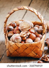 Hazelnuts and walnuts in a wicker basket in a rustic style, selective focus