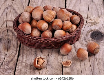Hazelnuts in a wicker basket on a wooden background close-up
