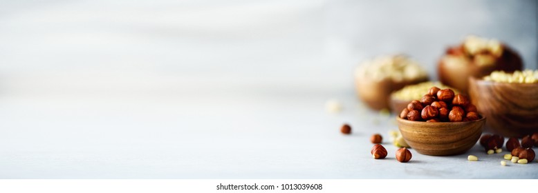 Hazelnuts in wooden bowl. Food mix background, top view, copy space, banner. Assortment of nuts - cashew, hazelnuts, walnuts, pistachio, pecans, pine nuts, peanut, raisins