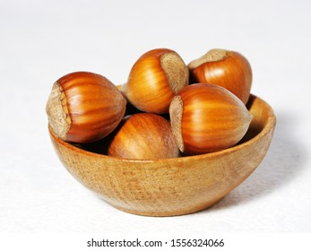 Hazelnuts in wooden bowl over white background