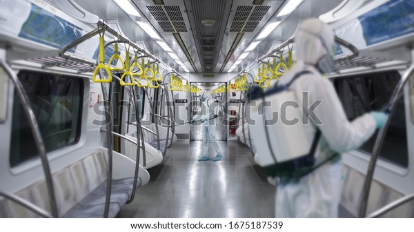 HazMat team in protective suits decontaminating metro car during virus outbreak