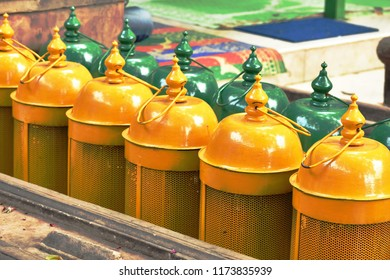 At Hazrat Nizamuddin Dargah, new delhi india, there are many lamps for use in night. there yellow and green lamps makes an colourful and eye catching pattern.