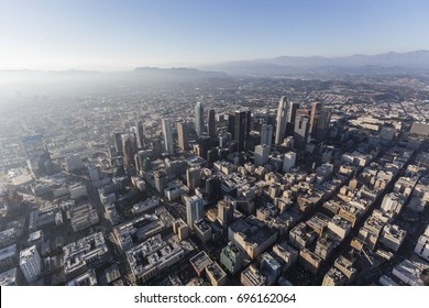 Hazy afternoon aerial view of urban downtown streets and buildings in Los Angeles, California.