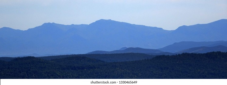 Hazy blue mountains receding into the distance as seen from the Mogollon Rim in Apache-Sitgreaves National Forest in Arizona