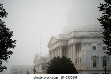 A hazy and blurry photo of the US Capitol building on a foggy morning where only some parts of the building is visible. The fog created a blurry mysterious look and camera noise like image.