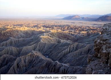 Hazy hot vast desert landscape with mountains, ridges, valleys, bathed in evening light