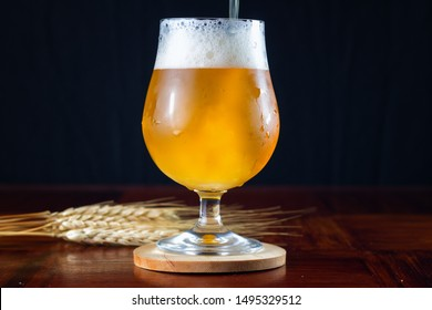 Hazy IPA craft beer being poured into a tulip shaped beer glass.